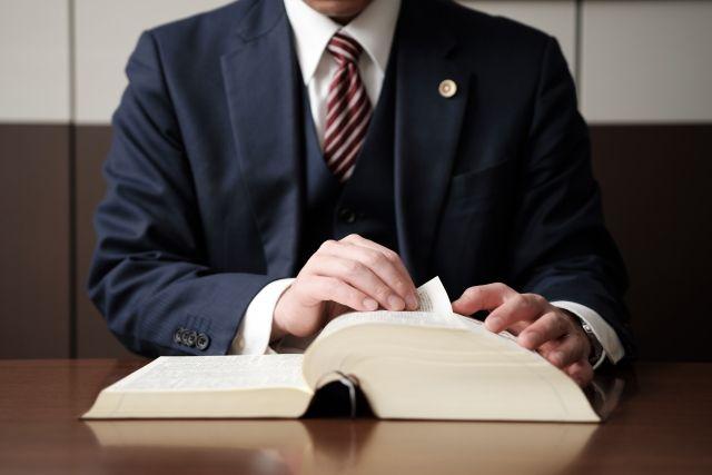 六法全書をめくる弁護士
