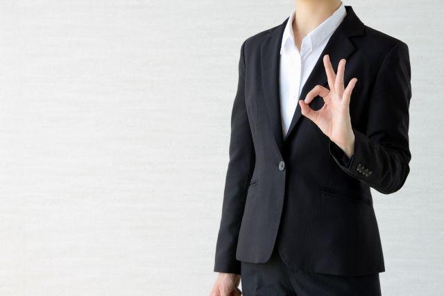 OKサインを出すスーツを着た女性